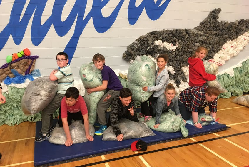 Members of the Spring Street Academy Sustainability Squad stand and kneel in front of the mural on the wall of the gymnasium. Students at the school collected more than 20,000 plastic bags – many of which were created into a temporary mural depicting a marine scene.