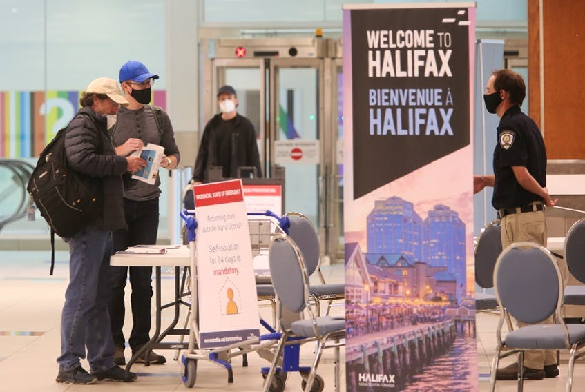 Passengers arriving at Halifax Stanfield International Airport are screened by a provincial health inspector in this July 2 photo. On Thursday, a passenger arriving from St. John's expressed concerns after lineups for arrivals from within and outside the Atlantic Bubble were mixed due to a high level of activity.