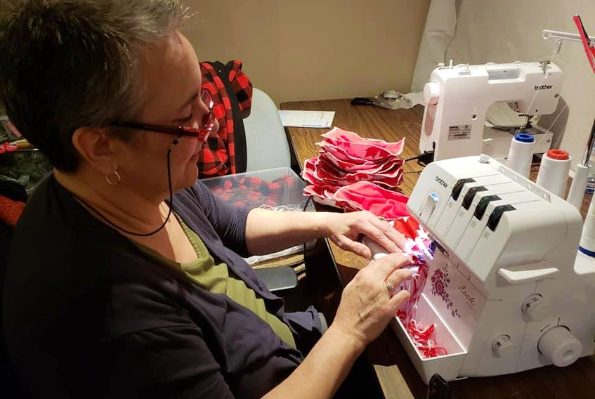 As business slows to a crawl thanks to COVID-19, Maritime Tartan Company's Sherrie Kearney is devoting her time to making facial masks, which will be traded for charitable donations to worthy causes. - Contributed