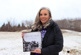 Amanda Carvery-Taylor holds up her new book called A Love Letter to Africville at a field near her home in Halifax on Sunday, Feb. 7, 2021. The book is a compilation of personal stories and photos from former residents of Africville, including Carvery-Taylor's own father, Frank Carvery.