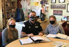 Kevin Veniot, principal of Northeast Kings Education Centre, sits with students Leah Bent and Emily Rutt at the school on March 12, 2021. Veniot said the school has adapted well to the turbulent pandemic year thanks to lots of prepration and co-operation among staff on technological changes.