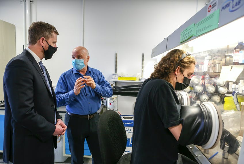 March 29, 2021 - Dr. Jeff Dahn, centre, shows Premier Iain Rankin an experiment a student is working on in an argon atmosphere at the Dalhousie Physics and Atmospheric Science Lab.