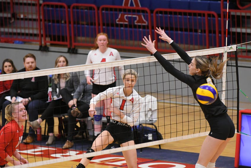 Acadia Axewomen's Peyton DeWolfe (1) spikes past the block of Dalhousie Tigers' Victoria  Turcot during AUS women's volleyball action on Sunday in Wolfville. The Axewomen handed Dalhousie its first loss of the season. Peter Oleskevich