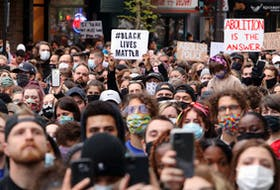 Thousands of participants 'take a knee' during an event along Spring Garden Road in Halifax Monday, June 1, 2020. The event was held in solidarity to peaceful rallies held in the United States protesting the death of George Floyd last week by a Minneapolis police officer who knelt on the man's neck.