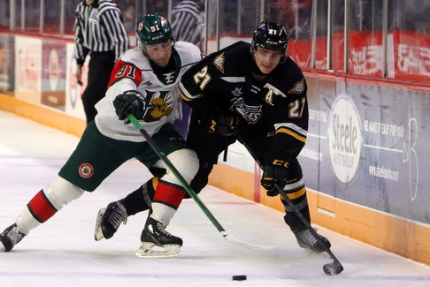 Elliot Desnoyers tried to force Cape Breton's Liam Kidney against the boards as the Eagles press during first period action.