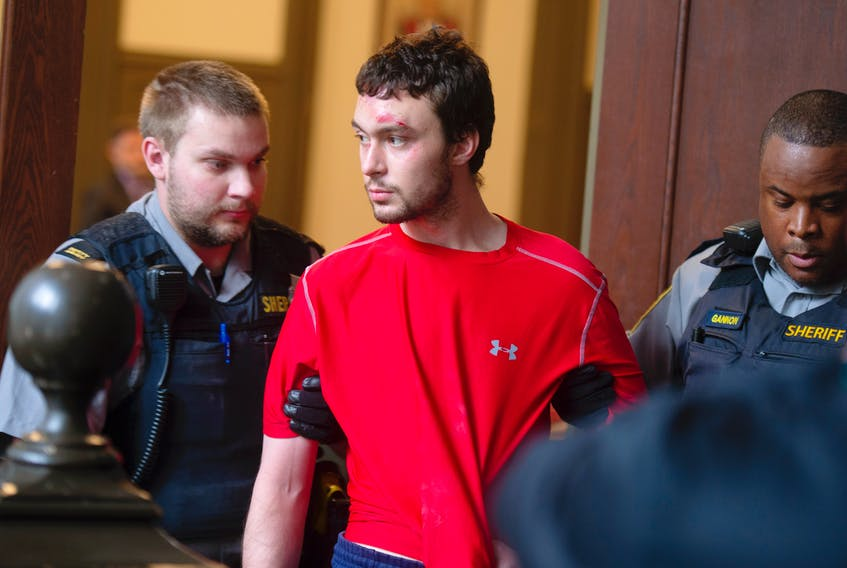 Ryan Richard Lamontagne is escorted into a courtroom at Halifax provincial court on Wednesday, Oct. 23, 2019. Lamontagne, 26, is charged with the second-degree murder of his mother.
