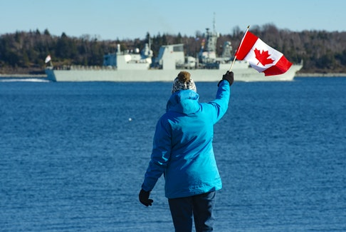 Mary MacAfee waves a Canadian flag as she watches HMCS Halifax leave on a six-month deployment as part of NATO's Operation Reassurance on Friday, January 1, 2021. MacAfee's son-in-law Petty Officer Phil Hudson is aboard the Halifax.