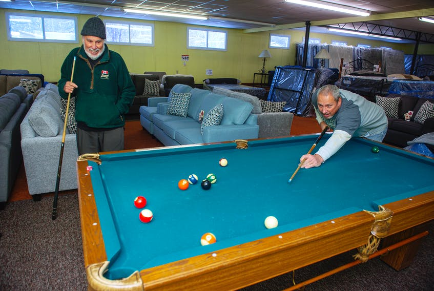 Abe Younis (left) and his son Yama play on the pool table inside the Abe's Furniture showroom in Mahone Bay on Friday, Jan. 25, 2021. Yama took over the business from Abe decades ago, but Abe can often be spotted hanging around the store.