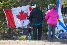 Garry Rogers and his wife Stella place a Canadian flag at a memorial at the end of Portapique Beach Road on Wednesday, April 22, 2020. Rogers lives in Truro but is originally from Cape Breton. He wanted to place the flag on behalf of the people of Cape Breton who can't come in person to express their condolences.
