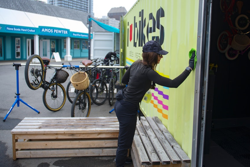 Sarah Craig, owner of I Heart Bikes, cleans the walls at her Halifax shop on Thursday, June 25, 2020. This is the 10th season for the waterfront business.
