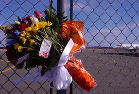 A bouquet of flowers is tied to the gates of the Cougar Helicopters facility at St. John's International Airport on Friday, March 13, 2009, the day after Cougar Flight 491 crashed in the Atlantic Ocean, killing 17 of the 18 people on board.
