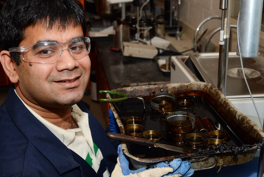 Kamal Hossain, an assistant professor of civil engineering at Memorial University, displays a pan of samples of oil that are used to make asphalt, in his MUN lab on Thursday morning.