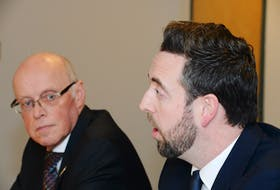Health Minister John Haggie (left) and Justice Minister Andrew Parsons speak to reporters Wednesday at the Confederation Building.