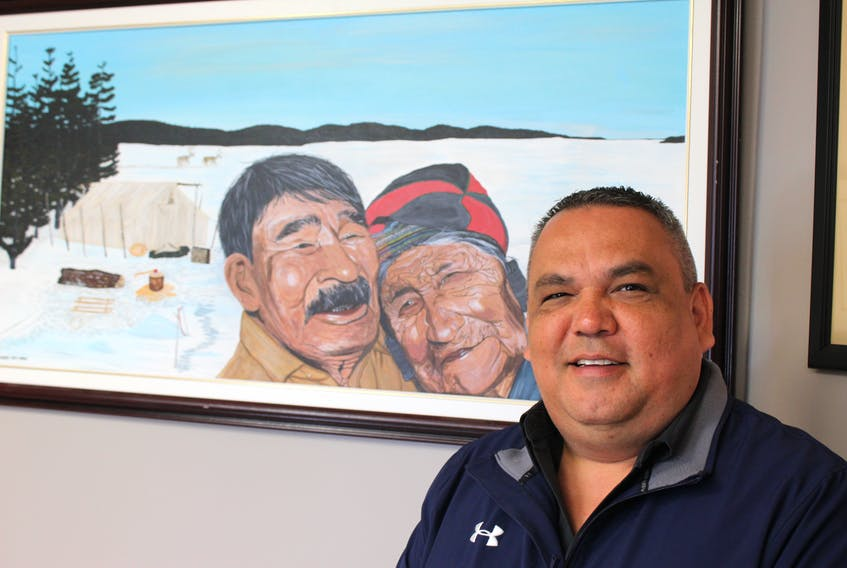 Chief Eugene Hart of the Sheshatshiu Innu First Nation stands beside a portrait of his grandparents, Mary Pasteen and Michel Pasteen, in his office in Sheshatshiu. The portrait was painted by Innu artist Mary Ann Penashue.
