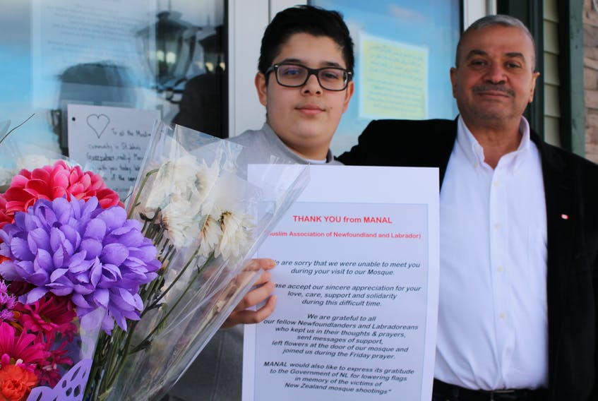 Moein Shahwan (right) and his son, Abdullah, are among the members of the Muslim Association of Newfoundland and Labrador who take comfort in the outpouring of support from the public after last week's devastating attack in New Zealand. People have been leaving flowers and other mementos in front of the St. John's mosque.