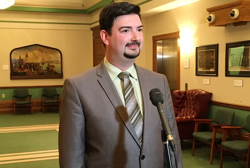 Culture Minister Christopher Mitchelmore speaks to reporters Monday outside the House of Assembly.