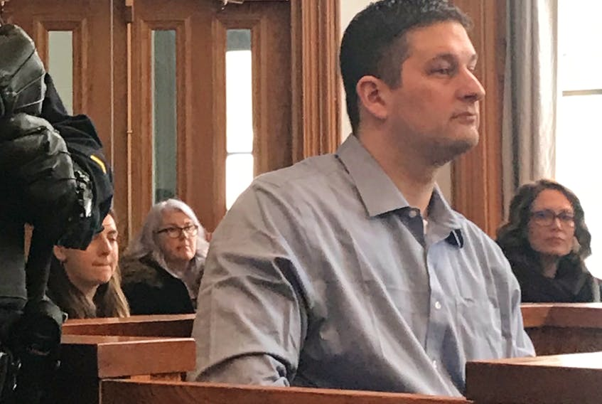 A sheriff's officer stands next to accused murderer Trent Butt as he sits in the prisoner's box awaiting the start of his trial Wednesday. Butt has admitted to causing the death of his daughter, Quinn, 5, but says he didn't plan to do it and doesn't remember it.