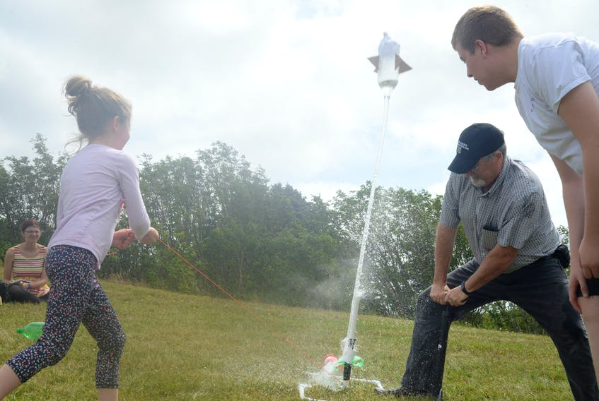 One of the summer camp participants launches their team's bottle rocket with the assistance of former schoolteacher John Barron, now program co-ordinator for Brilliant Labs, Wednesday on the large green-space embankment on the west end of the College of the North Atlantic campus on Prince Philip Drive.