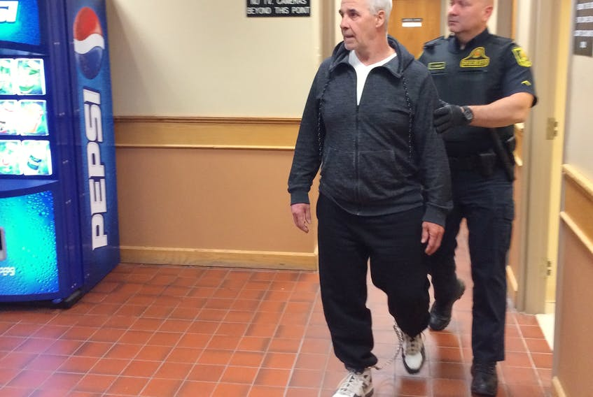 Dennis Murphy leaves a St. John's courtroom accompanied by a sheriff's officer June 17, 2019.