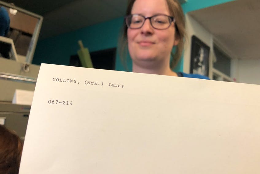Archival assistant Nicole Penney holds an index card showing one of the many women who were identified by their husband's names – in this case, a Mrs. James Collins.