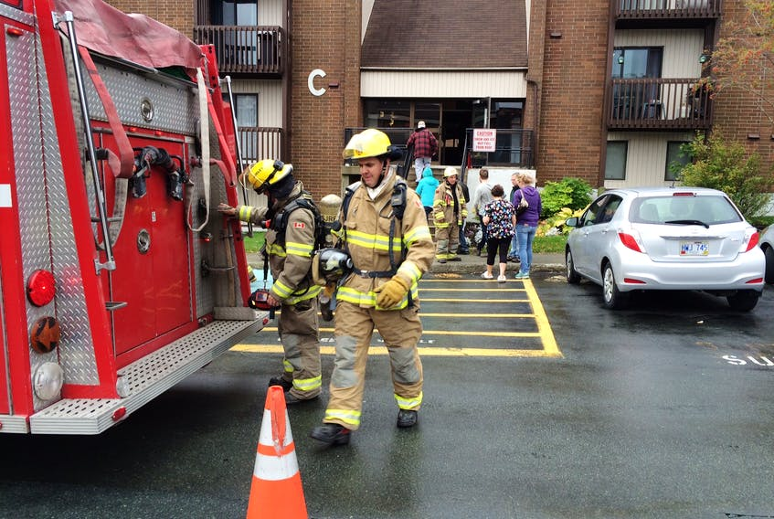 Firefighters leave Building C at the Torbay Estates apartment complex in St. John's Friday after a minor fire.