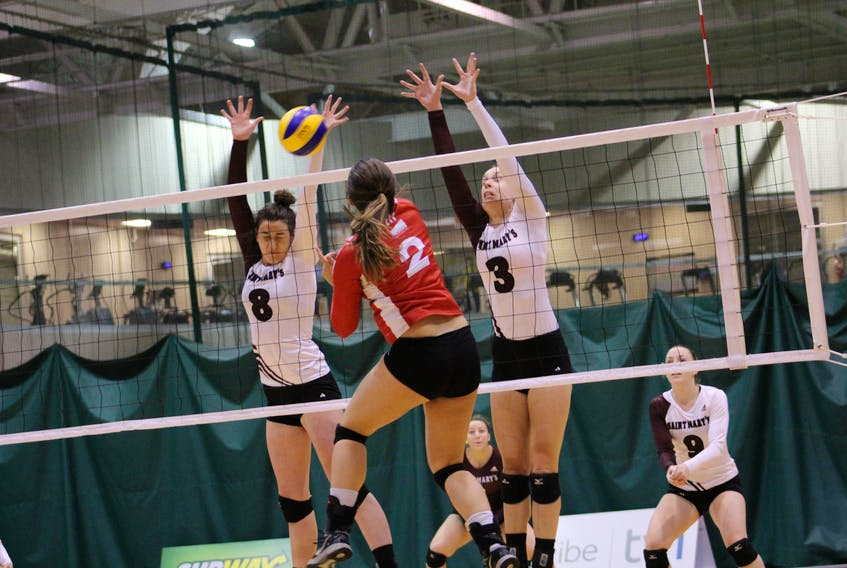In the file photo from the Atlantic University Sport 2016-17 women's volleyball season, Memorial University's Kierstin Fey blasts a shot as Lindsay Donovan (8) and Kristina Adler (3) the Saint Mary's Huskies attempt to defend during a game at the Field House in St. John's. With AUS most valuable player Jill Snow having graduated, Sea-Hawks head coach John Slauenwhite is counting on Fey to take over as the team's outside hitter.