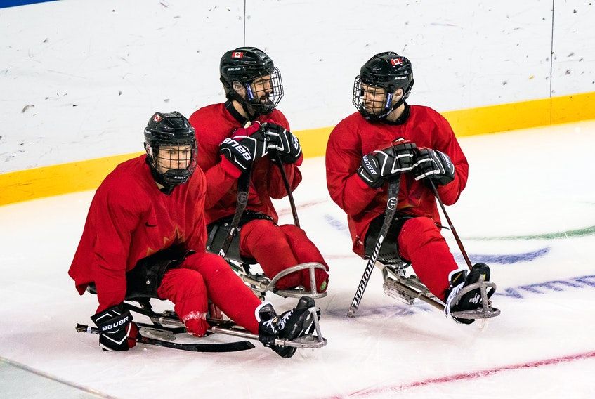 Liam Hickey (left) of St. John's, along with team captain Greg Westlake and Tyler McGregor, are shown during a practice for Canada's sledge hockey team ahead of the start of competition at the 2018 Winter Paralympic Games in Pyeongchang, Korea. — 
