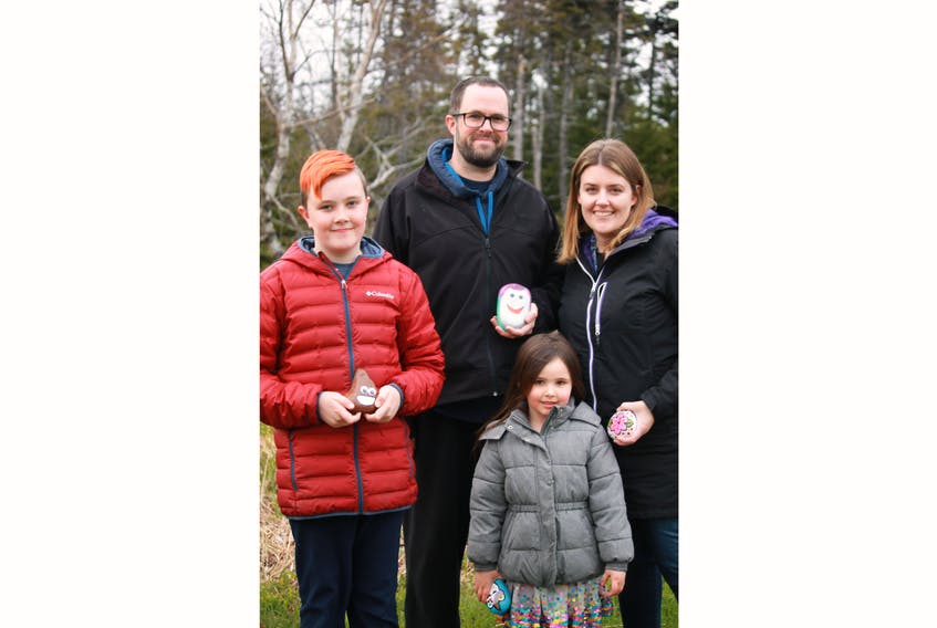 The Dawe family (from left) Alex, Bradley, Elizabeth and Kelli, left some more painted rocks at the Virginia River Trail in St. John's on Friday. — Jasmine Burt/Special to The Telegram