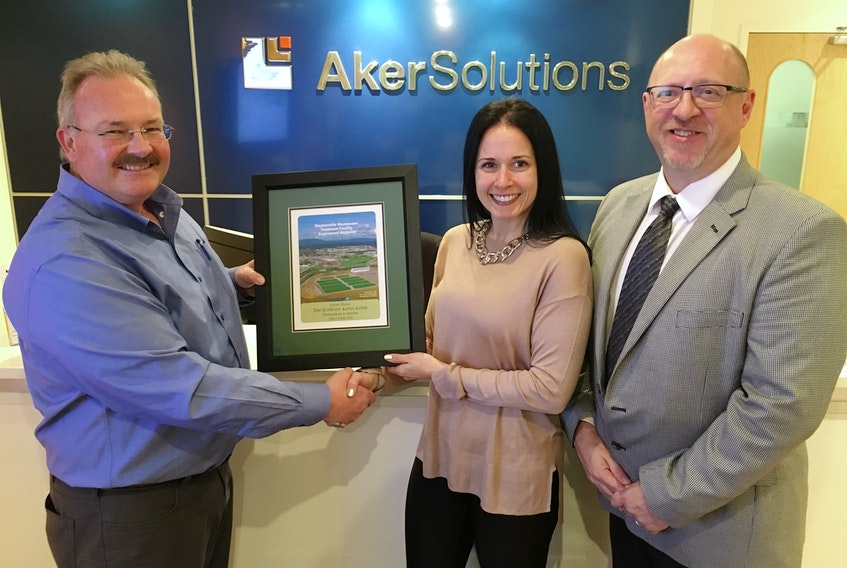 Glenn Sharp (left) presents an official Newfoundland Climate and Ecosystems Conservancy Project carbon credit to Aker Solutions Canada HSE manager Melissa English-Barbour and vice-president and general manager Dave Billard.