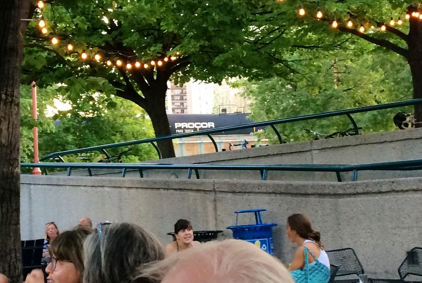 People relax in The Forks  in downtown Winnipeg. In the distance, peeking through the trees, a train tanker car trundles by.