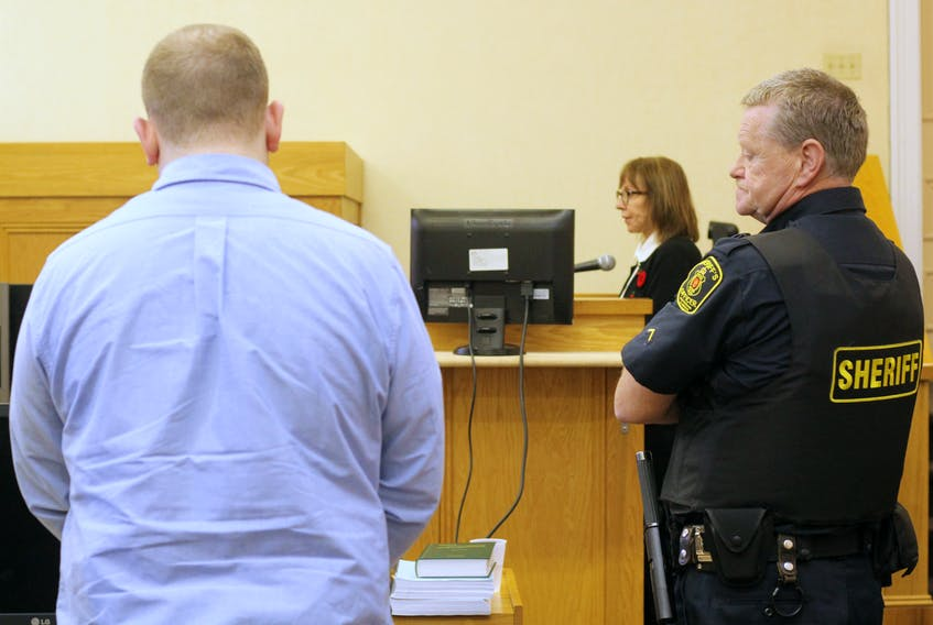 Brandon Phillips stands in Courtroom No. 4 at Newfoundland and Labrador Supreme Court in St. John's Friday morning, as Linda McBay prepares to resume her testimony after a break.