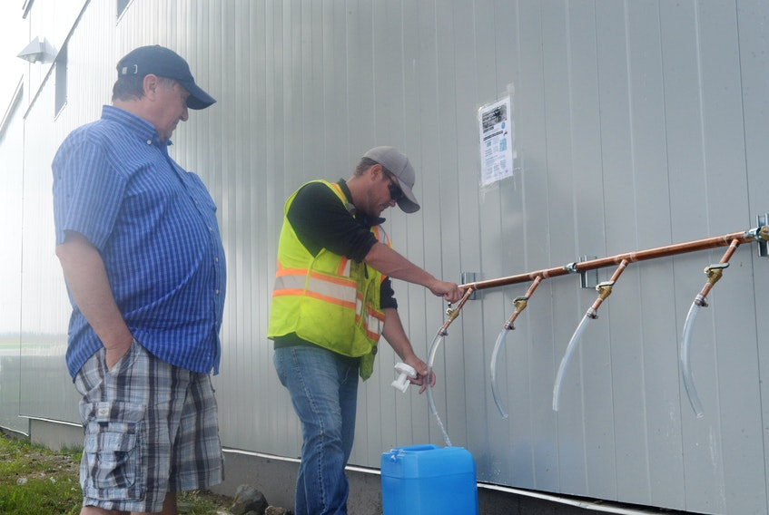 Cowan Heights resident Roger Hollahan (left) gets a five-gallon container of water filled by a City of St. John's waterworks department employee — who didn't want to give his name — at the Blackler Avenue depot on Wednesday afternoon.