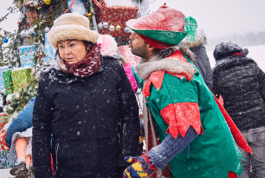 """Shaun Majumder, as gravedigger Cyril Pippy, puckers up for a kiss from Mamie Lou Furey (Mary Walsh) in a scene from """"Christmas Fury,"""" airing on CBC-TV Sunday night."""