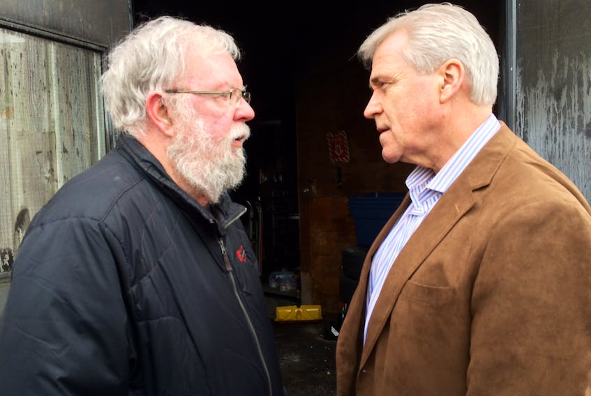 """Community Food Sharing Association executive director Eg Walters (left) chats with Premier Dwight Ball outside the CFSA's warehouse on Topsail Road, where fire ripped through the facility that housed the food supply for many community food banks. Before leaving, Ball was heard telling Walters, """"A nice new food bank will rise from the ashes."""" — Photo by Joe Gibbons/The Telegram"""