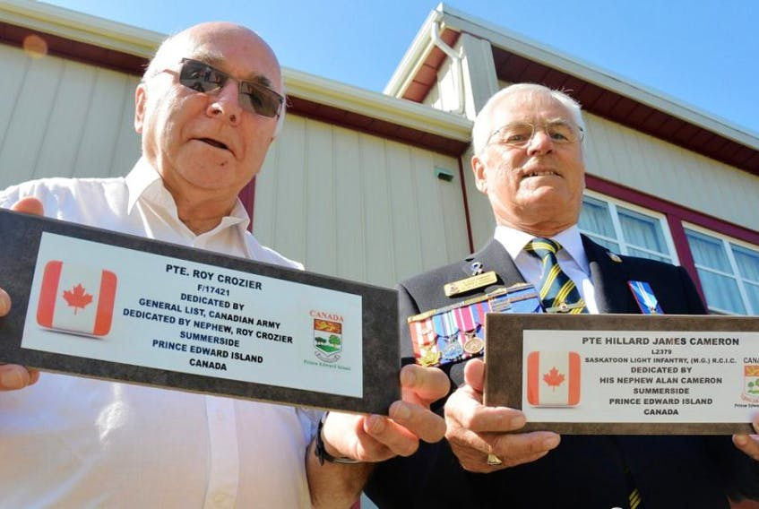 Roy Crozier, left, and Alan Cameron, right, hold two plaques they plan to lay at the graves of their uncles who died in the Second Word War. Both are buried in the same war cemetery in the U.K. and their nephews have always wanted to visit their graves.
