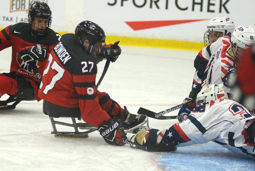USA goalie Steve Cash covers a loose puck before Canada's Brad Bowden can get to it during Wednesday's World Sledge Hockey Challenge at MacLauchlan Arena.