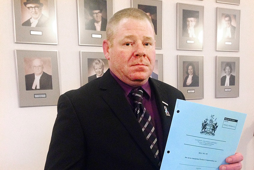 CUPE local president Jason Woodbury holds a copy of legislation that will see PTSD covered under the Workers Compensation Act. Woodbury has spent at least four years trying to bring about this change to P.E.I.  ©THE GUARDIAN