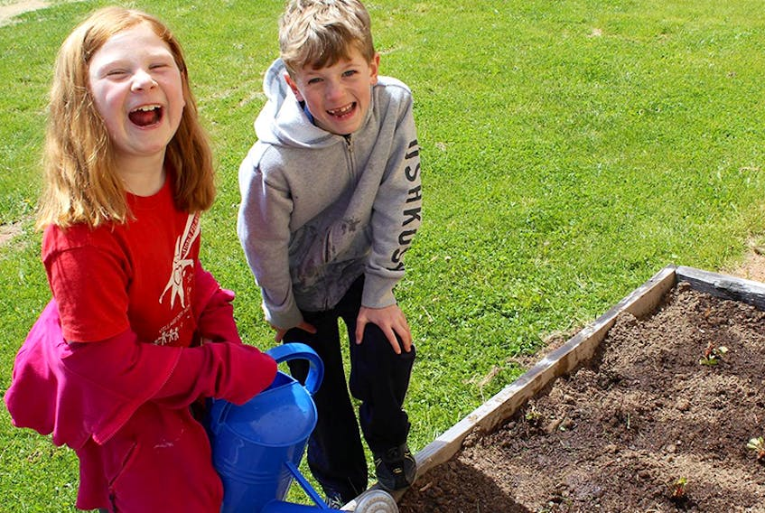 Sophie Hilton and Dylan Andrews-Christian work in the garden at the early childhood centre, Les petits rayons de soleil, in Rustico, which was set up by various partners and gardening projects, including one that was funded through Farm Credit Canada's Expression Fund.  ©THE GUARDIAN