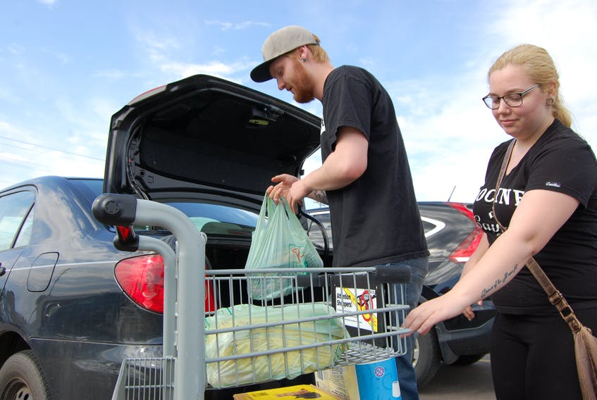 Elijah Henderson and Kyla MacKenzie unload plastic bags full of groceries at the Atlantic Superstore Thursday. A bill to ban plastic shopping bags is working its way through the legislature and is ready for the third and final reading.