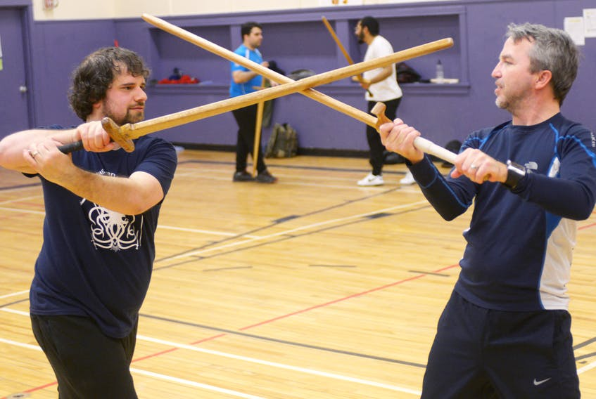 Evan Hill, left, and Michael Smallwood, right, battle with some wooden long swords during a Maritime Sword School practice at St. Jean Elementary School in Charlottetown on Jan. 21, 2018.