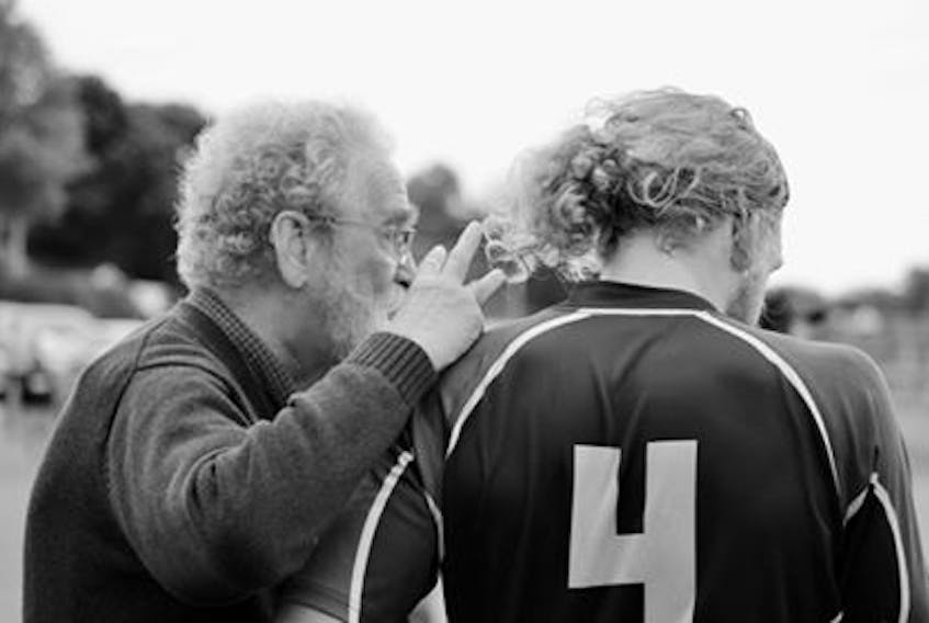Raymond Moore, left, is pictured counselling a player on the sideline of a rugby pitch. Moore is going into the P.E.I. Rugby Union Hall of Fame for his work as an organizer, coach and administrator.