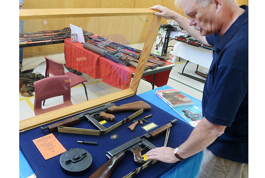 """Sackville resident Peter Ripley shows his Thompson submachine guns during the third annual P.E.I. Gun and Memorabilia show at North Shore Community Centre on the weekend. The firearm, often referred to as a """"Tommy gun,"""" is one of the most recognizable in the world but is prohibited to most Canadians.  ©THE GUARDIAN/Mitch MacDonald"""