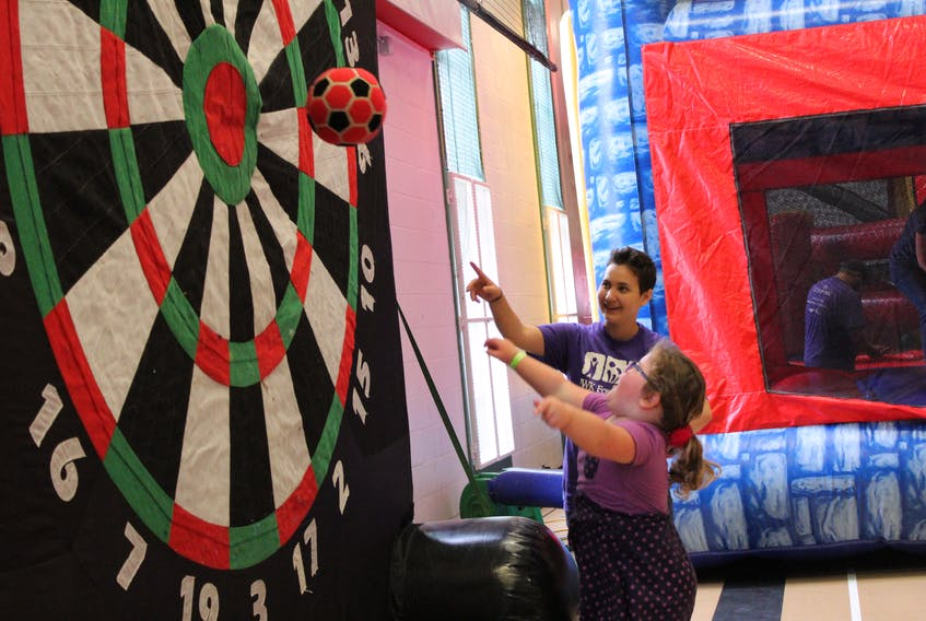 Isla James Smith, 5, was excited to hit the bull's-eye during activities at the IWK Foundation Telethon held at the Murphy Community Centre in Charlottetown on Sunday afternoon. Helping to encourage her was volunteer Aysha Duilsse. Results of the annual event, which brings in money from across the region, were not available by press time.
