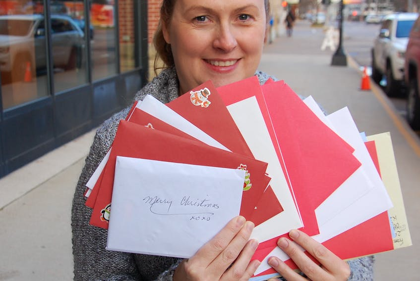 Suellen Clow-Munro, sales and marketing manager of The Holman Grand Hotel, fans out some of the many Christmas cards collected at the hotel that will soon be delivered to residents of Andrews of Charlottetown and Andrews of Stratford.