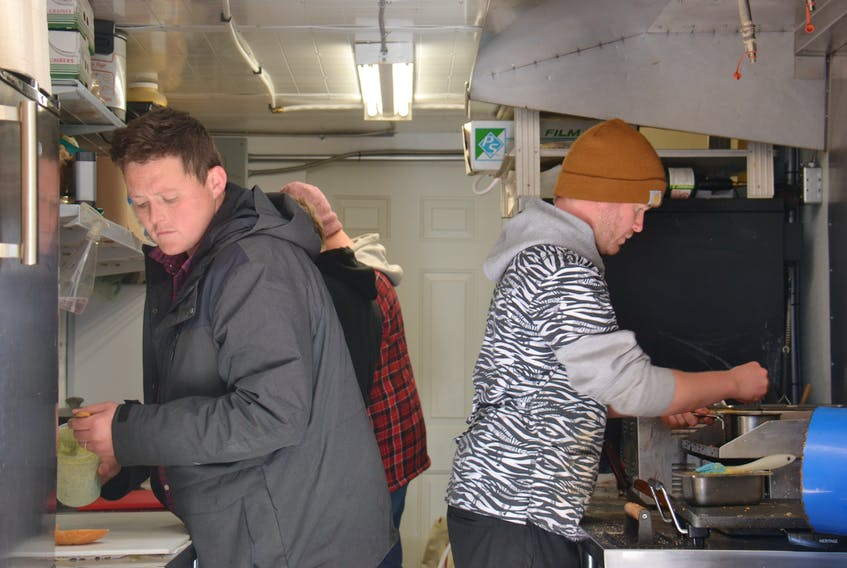 It's business as usual on Tuesday for Nimrods' and co-owners Mikey Wasnidge, left, and Jesse Clausheide, shown at work in their truck's kitchen at its current location on the corner of Allen Street and St. Peters Road in Charlottetown.