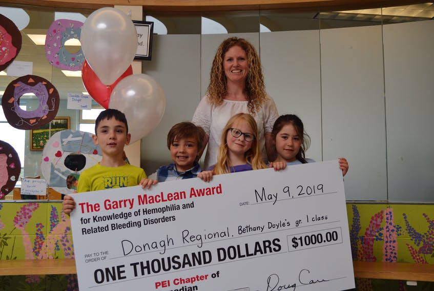Bethany Doyle is shown with some of her Grade 1 class at Donagh Regional School as they proudly display the $1,000 cheque they were awarded by the P.E.I. chapter of the Canadian Hemophilia Society for bringing awareness to the disorder. The students pictured are, from left, Ezra DesRoches, 6, Mason Doran, 6, Hope Quinn, 6, and Kally MacDonald, 6.