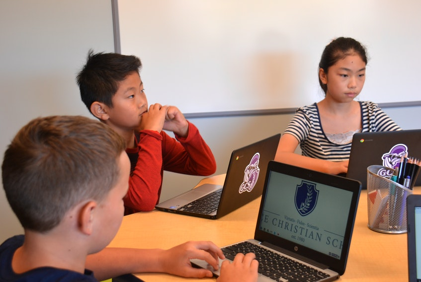 Jayden Somers, left, Jason Sin, and Kate Shi, right, work on their new Chromebooks in a newly remodelled classroom at Grace Christian School on Sept. 10. Kai Vere/The Guardian