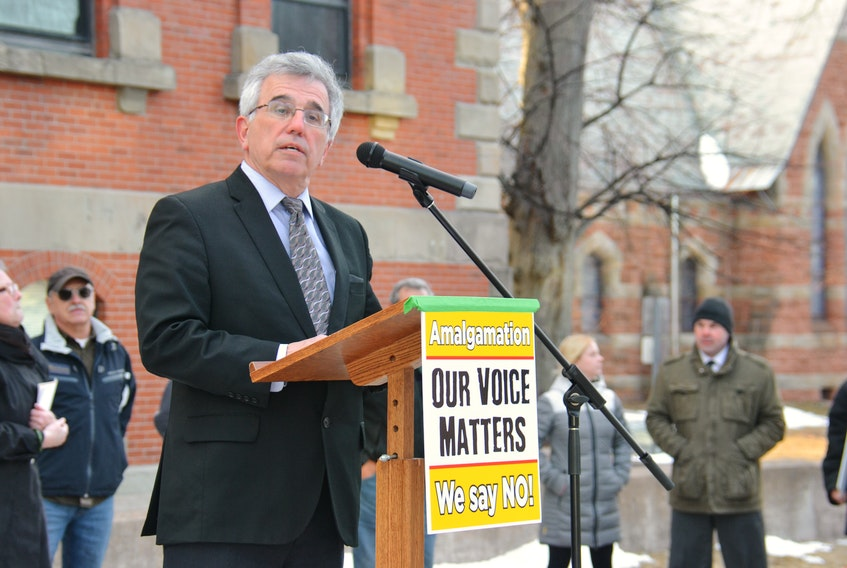 Communities Minister Richard Brown speaks to protesters outside the legislature in Charlottetown Tuesday afternoon.