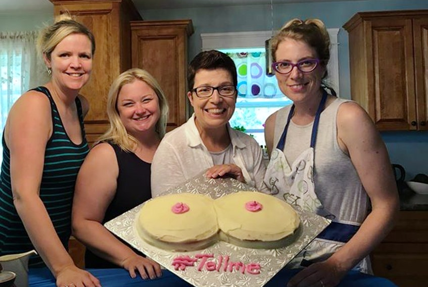 Kathy Kaufield, second from the right, displays a cake baked by volunteers involved with the #TellMe campaign. Kaufield, who lives in New Brunswick and is originally from Stratford, P.E.I., started the campaign to raise awareness about how mammograms can miss tumours from women with dense breasts.