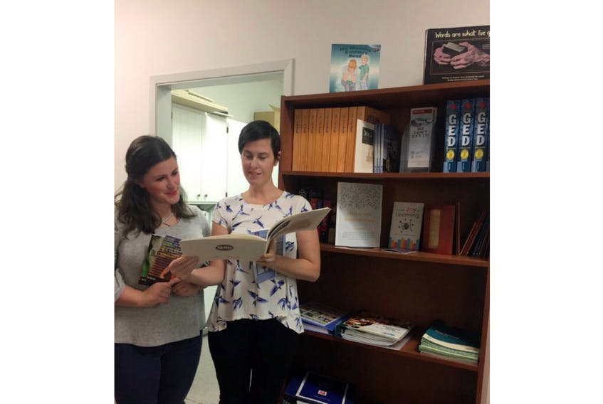 Jinny Greaves, right, and Katie Duffy pose next to the P.E.I. Literacy Alliance's new Volunteer Literacy Tutor Library.